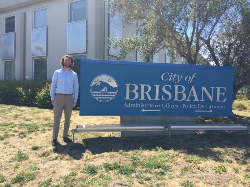 Daniel Fields next to Brisbane city offices sign