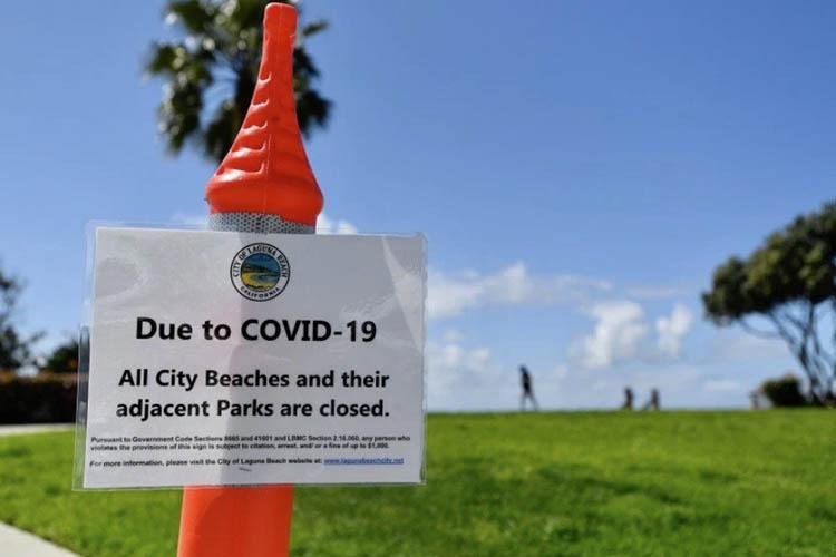 Photo of sign that says beaches and parks are closed due to COVID-19