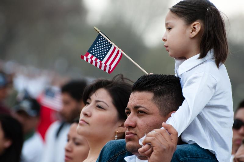 Photo of Latinx -American family with a mother, father, and daughter waving American Flag on her Dad's shoulders