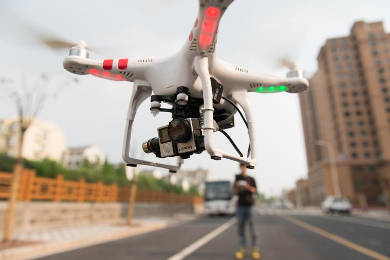 drone hovering with pilot in background
