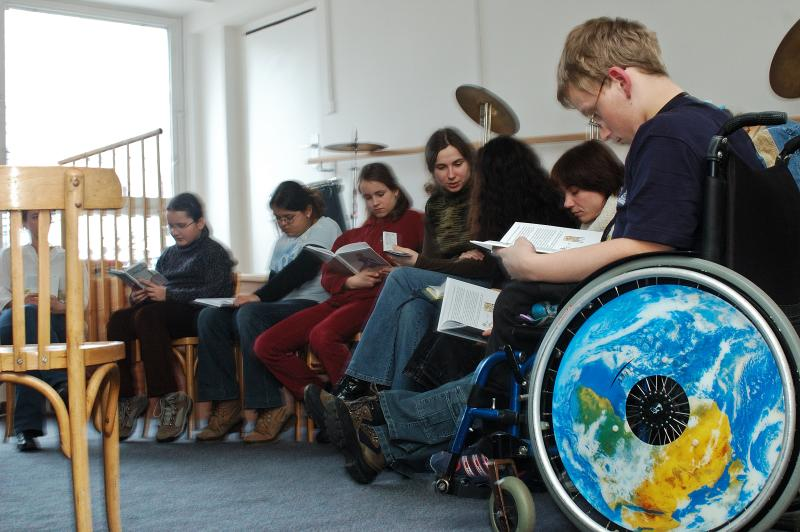 A class reads from books. A disabled student is in a wheelchair.