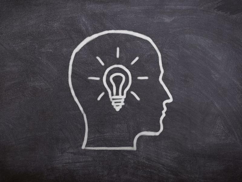 Chalk drawing of human head with lightbulb for brain