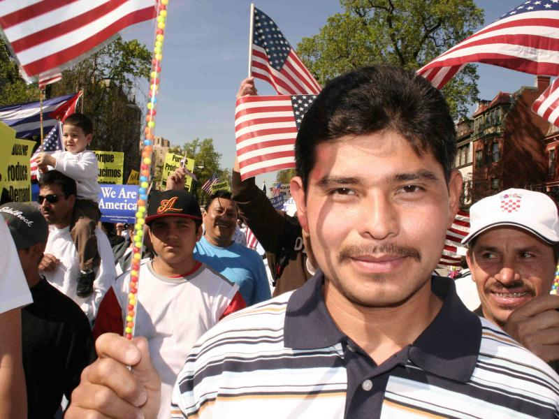 Immigrant rights march with young man carrying American flag