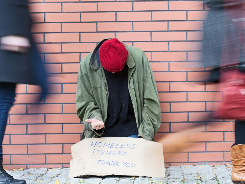 photo of homeless person and passerbys