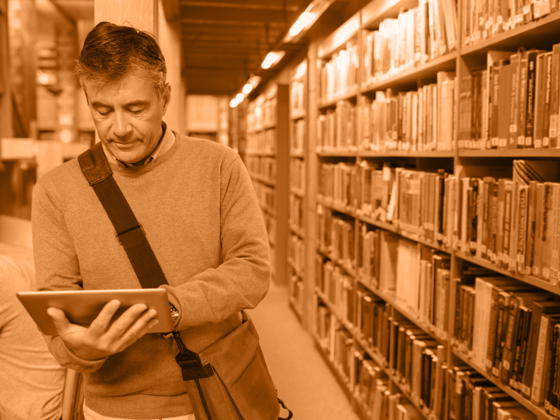 man in library stacks looking at ipad