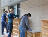 Restoring old furniture at the National Center for Children and Families as part of a UNIC volunteer event